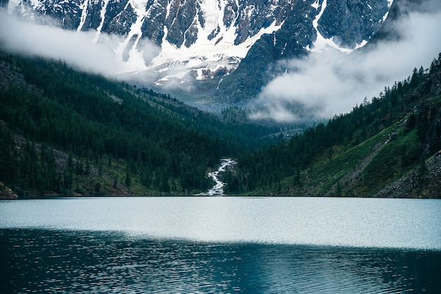 美しい大きな氷河、低い雲に囲まれた岩だらけの雪山、丘の針葉樹林、山の湖、高原の小川 Premium写真