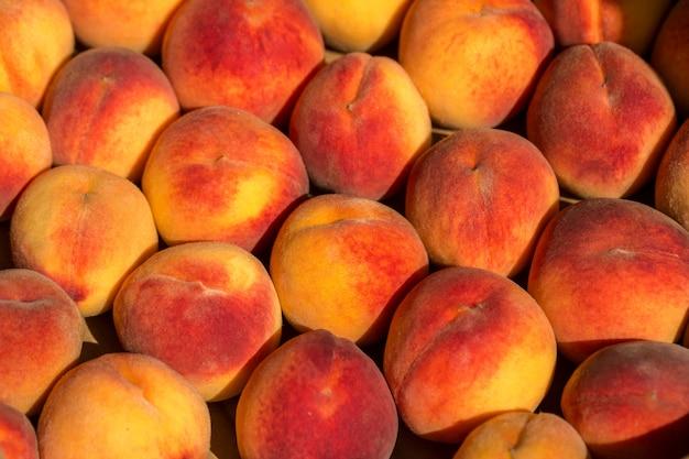 Beautiful big red peaches in a drawer. Premium Photo