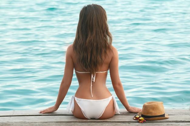 Beautiful in the bikini on the wooden pier Premium Photo
