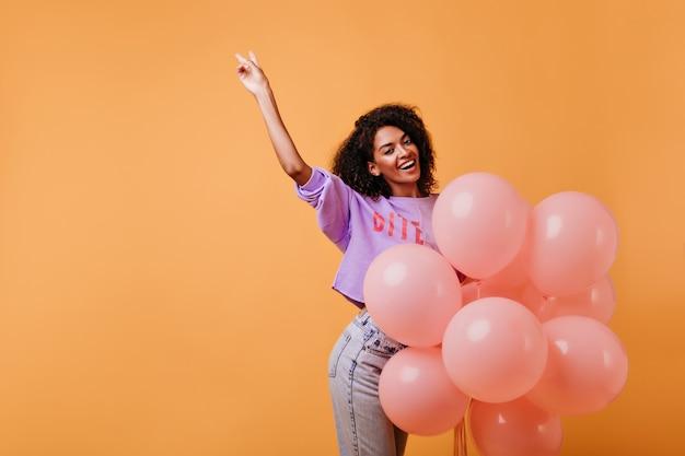 생일 파티를 준비하는 아름 다운 흑인 여성 모델. 이벤트 후 미소로 춤추는 보라색 셔츠에 세련된 아프리카 소녀. 무료 사진