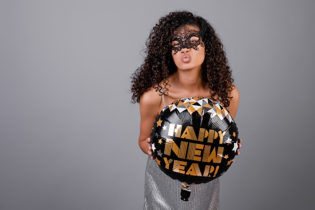Beautiful black girl with happy new year balloon wearing masquerade mask isolated over grey Premium Photo