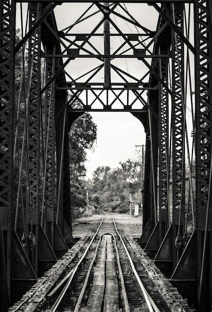 Beautiful black and white shot of a railroad on a metal bridge Free Photo