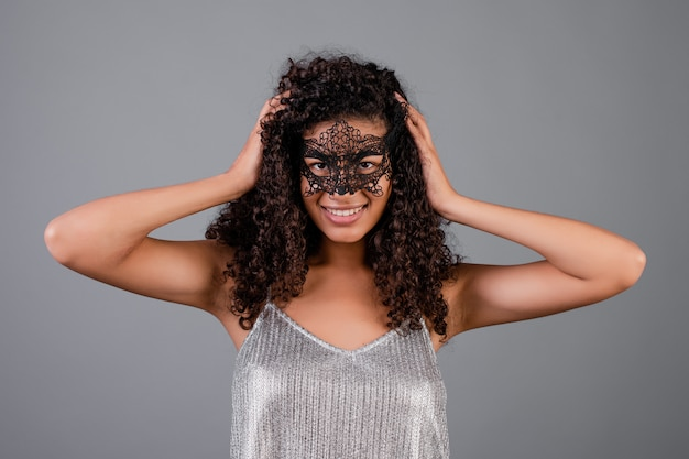 Beautiful black woman wearing elegant masquerade mask isolated over grey Premium Photo