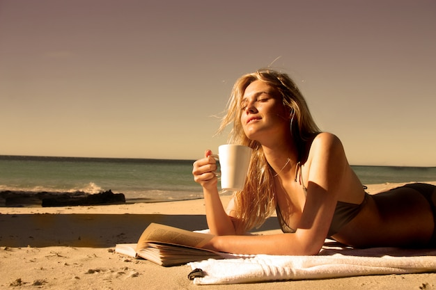 Beautiful blond girl drinking a cup of coffee and reading a book on the beach Premium Photo