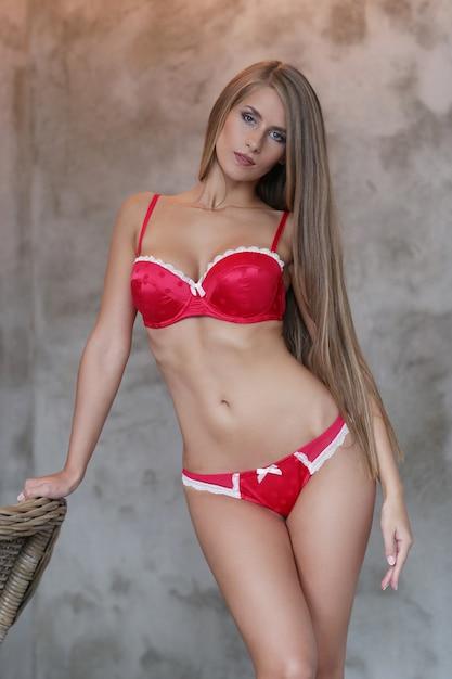 Красивая белокурая женщина позирует в красном нижнем белье Бесплатные Фотографии