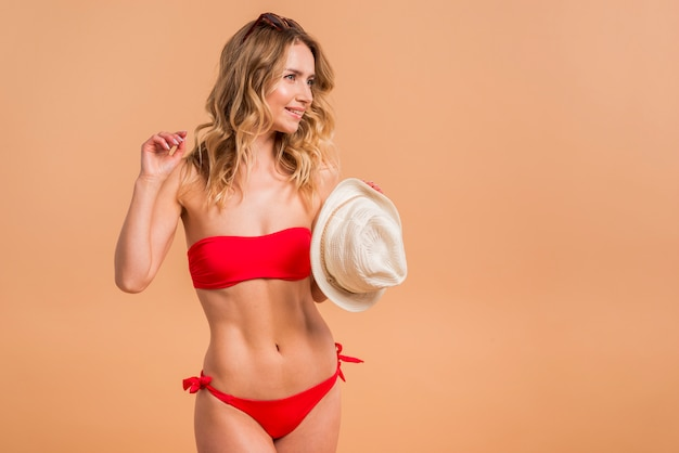 Beautiful blond woman in red swimsuit holding hat Free Photo