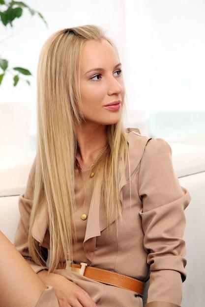 Beautiful blond woman sitting on a coach Free Photo