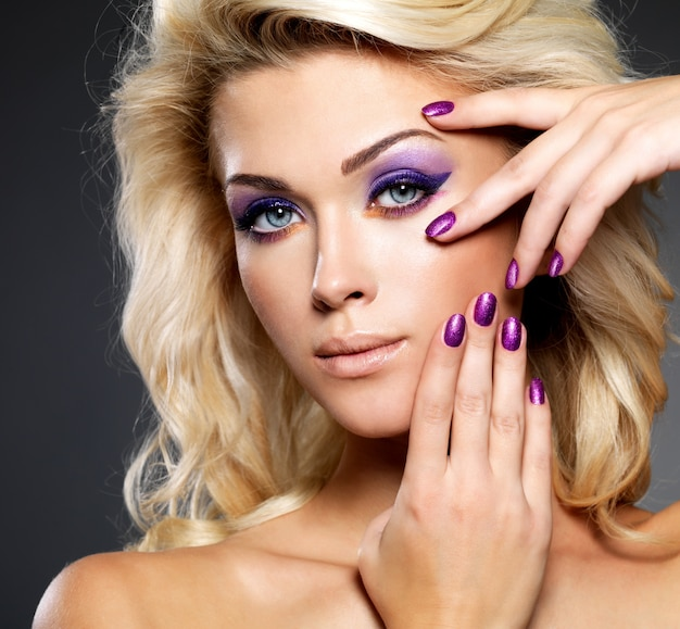 Bella donna bionda con bellezza viola manicure e trucco degli occhi Foto Gratuite