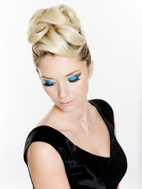 Bella donna bionda con l'acconciatura riccia e il trucco blu degli occhi isolati su bianco Foto Gratuite