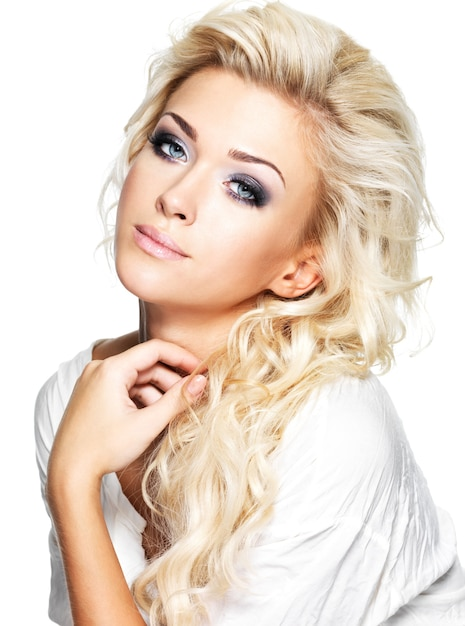 Beautiful blond woman with long curly hair and style makeup. girl posing on white space Free Photo