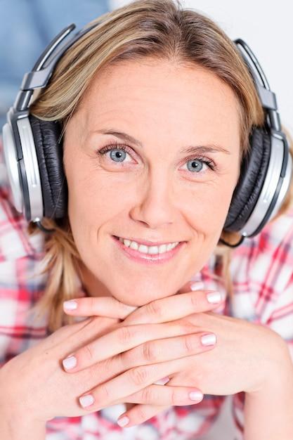 Красивая блондинка женщина, слушающая музыку в наушниках Бесплатные Фотографии