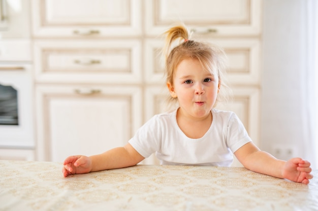 Beautiful blonde baby girl having breakfast in kitchen. funny faces Premium Photo