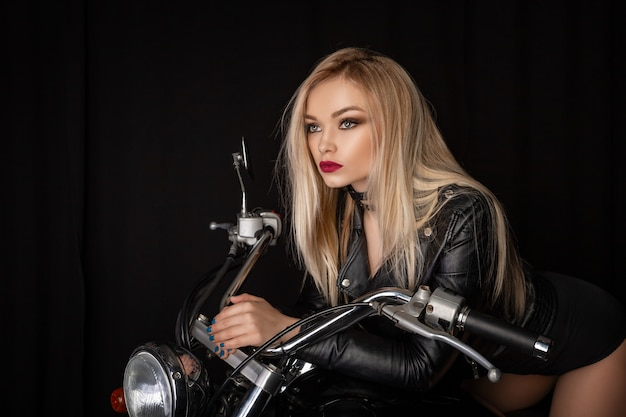 Beautiful blonde in a black leather jacket sitting on a motorcycle Premium Photo