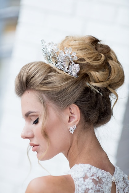 Beautiful blonde bride with high hair-do and precious silver wreath on her hair Free Photo