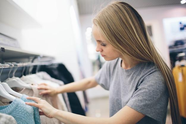 Красивая блондинка покупает обновки в магазине одежды. продавец работает в бутике Premium Фотографии