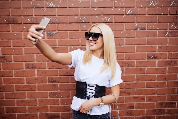 Bella bionda donna caucasica in piedi davanti al muro di mattoni e fare selfie. Foto Gratuite