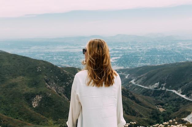 サングラスと自然の丘の上に立っている白いシャツの美しいブロンドの女性 無料写真