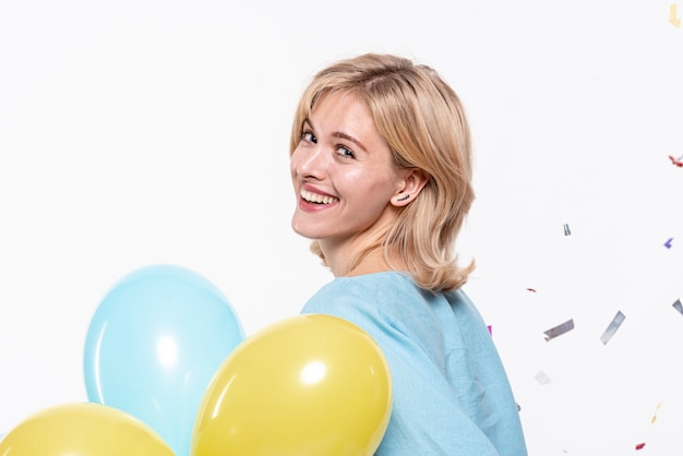 Beautiful blonde girl holding balloons Free Photo