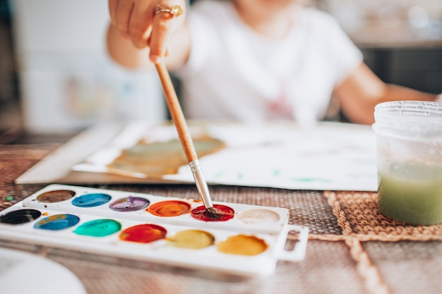 Beautiful blonde girl painting with paintbrush and water colors in the kitchen. kid activities concept. close up. toned. Premium Photo