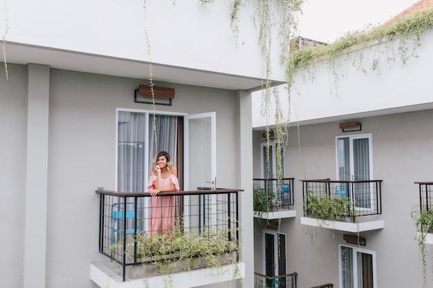 Bella ragazza bionda che posa al balcone dell'hotel. sorridente donna romantica in abito rosa godendo la mattina. Foto Gratuite