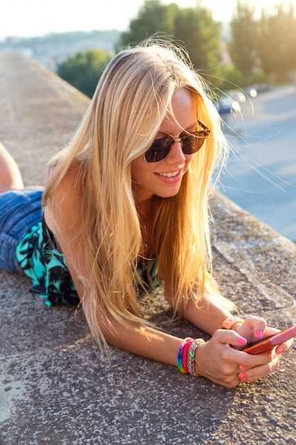 Fille Blonde Belle beautiful blonde girl sitting on the roof with mobile phone. photo