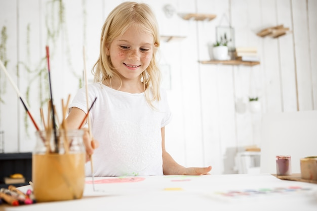 Beautiful blonde girl smiling and joyfully painting picture with brush Free Photo