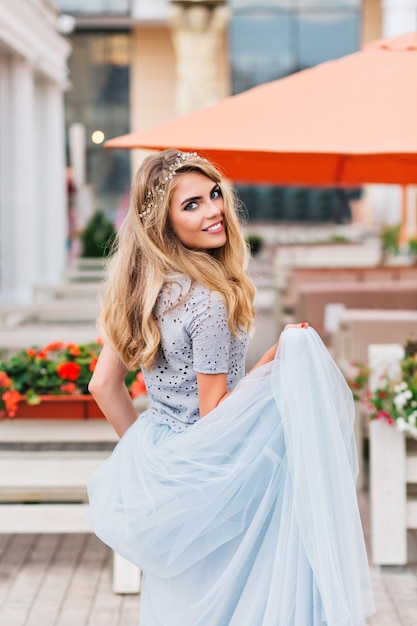 Bella ragazza bionda che cammina sul fondo della terrazza. tiene in mano una lunga gonna in tulle blu e sorride alla telecamera. Foto Gratuite