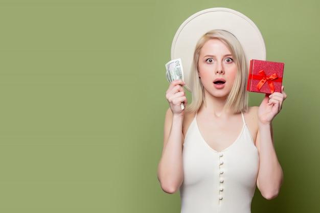 Beautiful blonde girl with money and gift box Premium Photo