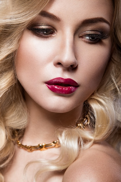 Beautiful blonde in a hollywood manner with curls, red lips Premium Photo