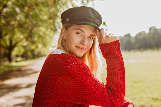 Beautiful blonde looking pretty in red pullover and trendy black hat standing in the park. smiling girl enjoys sunny autumn day. Free Photo