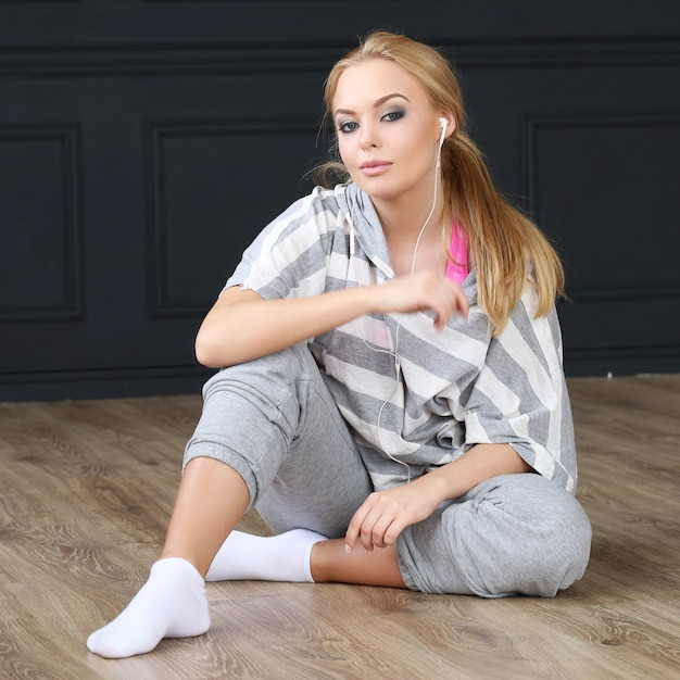 Beautiful blonde sitting on wooden floor Free Photo