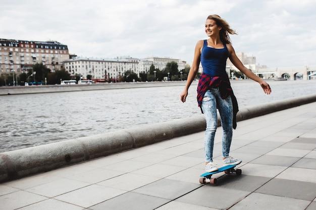 Beautiful blonde skateboard on the promenade Free Photo