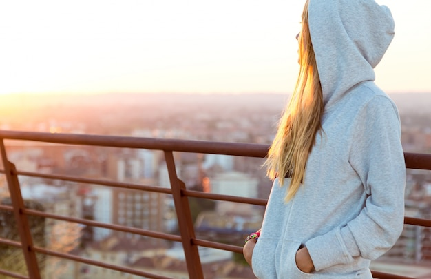 Beautiful blonde stands on the edge of the roof. Free Photo