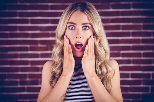 Beautiful blonde woman being shocked Premium Photo