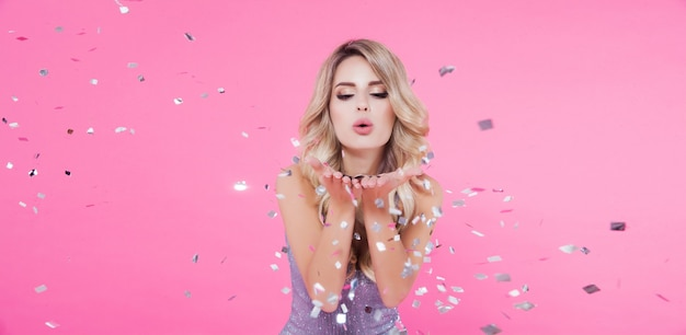 Beautiful blonde woman celebrating new year or happy birthday party throwing confetti on pink Premium Photo