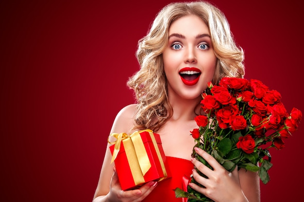 Beautiful blonde woman holding bouquet of red roses and gift Premium Photo