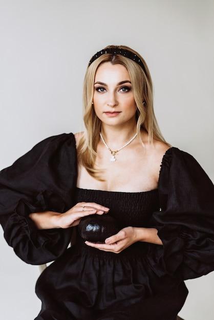 Красивая блондинка в черном льняном платье с тыквой в руках. этническая мода, натуральная ткань. хэллоуин вечеринка. мягкий выборочный фокус. Premium Фотографии