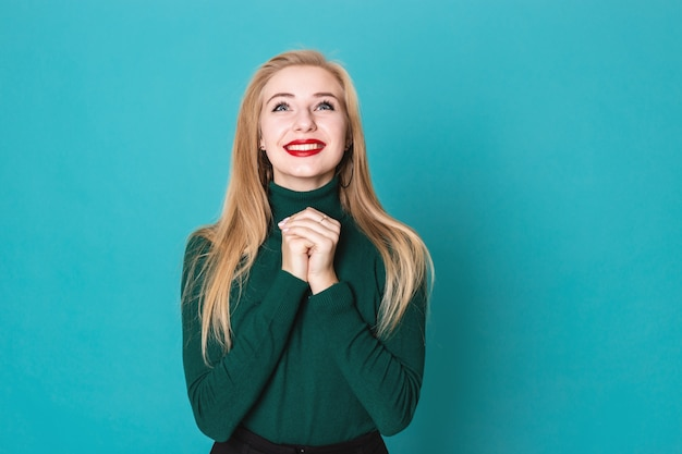 Beautiful blonde woman is grateful for something standing on a blue background wearing sweater Premium Photo