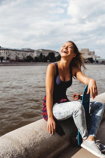 Beautiful blonde woman posing with a skateboard Free Photo