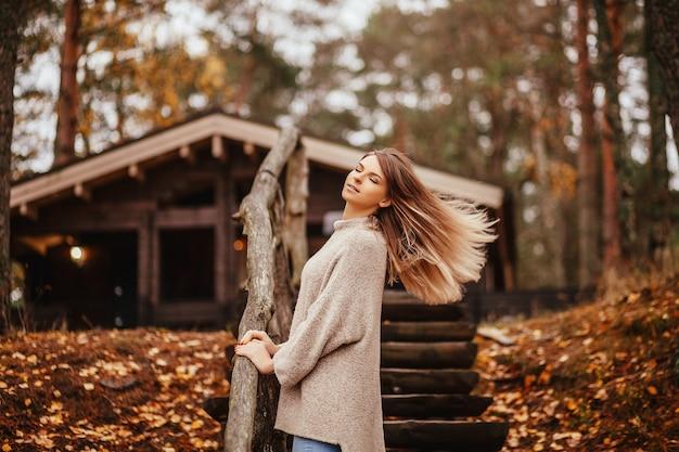 Beautiful blonde woman standing near the wooden stairway Premium Photo