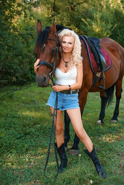 美しいブロンドの女性は、森の背景に自然の中で馬と一緒に立っています Premium写真