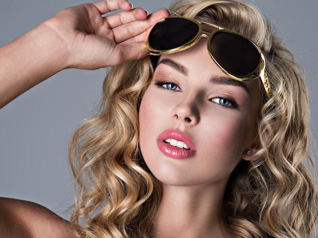 Красивая белокурая женщина с длинными волнистыми волосами. привлекательная молодая девушка носит модные солнцезащитные очки. сексуальная молодая взрослая девушка позирует в студии - портрет крупным планом Бесплатные Фотографии