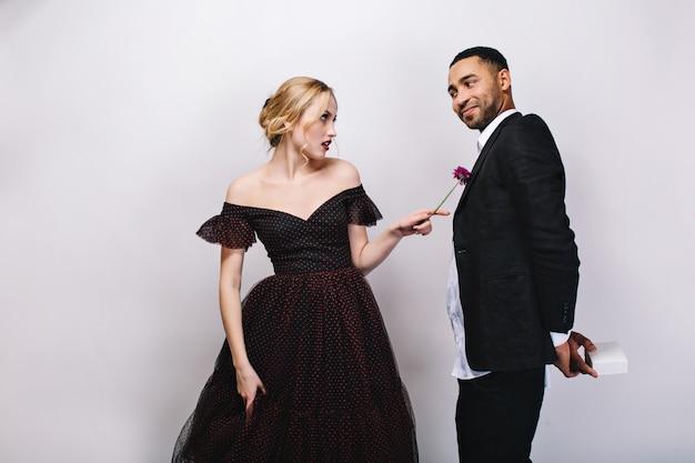 Красивая белокурая молодая женщина в роскошном вечернем платье, недовольно смотрящая на красивого парня в смокинге. забавные моменты прекрасной пары, делая сюрприз, день святого валентина. Бесплатные Фотографии