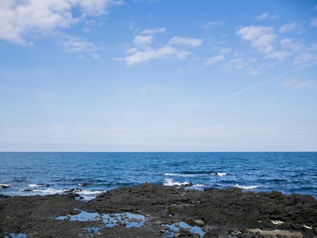 Beautiful blue sea with black sand beach and sky of jeju island in korean Premium Photo