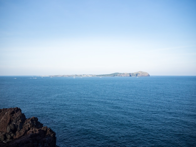 Beautiful blue sea with black sand beach and sky of jeju island in korean Premium Photo