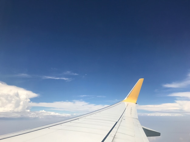 Beautiful of blue sky above the clouds with wings of the airplane Premium Photo