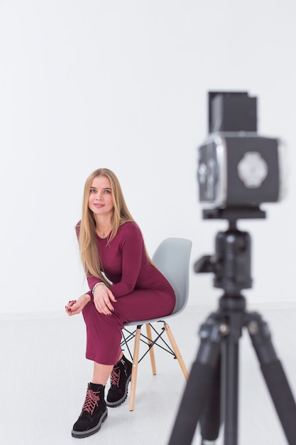 Beautiful blurred female model sitting on a chair in studio Free Photo