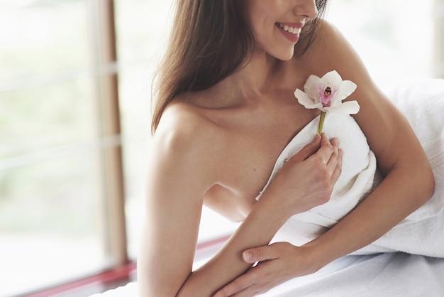 白い花の蘭とボディケアの美しいボディ女性。 無料写真