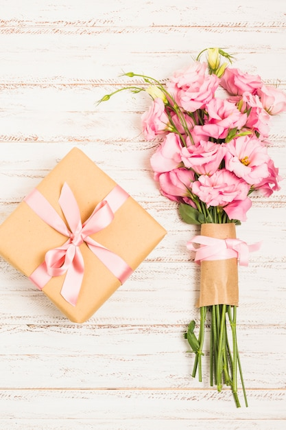 Beautiful bouquet of fresh pink eustoma flowers with present box on wooden surface Free Photo