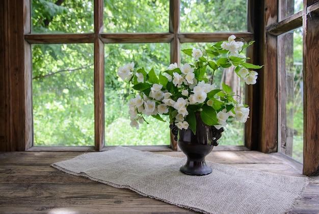 Красивый букет веток жасмина в вазе у деревянного окна на природе Premium Фотографии